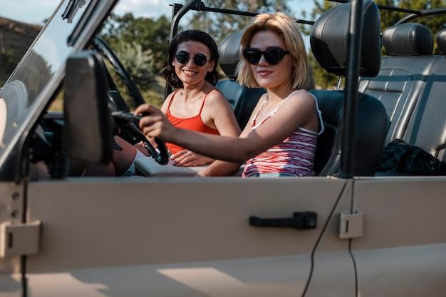 Amigas com óculos de sol viajando de carro