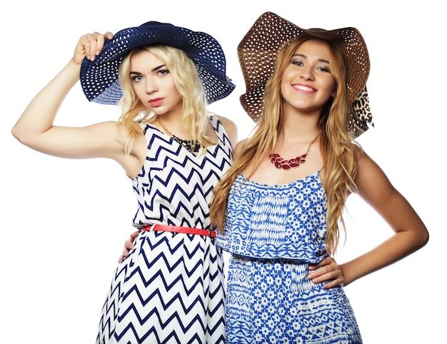 Amigas com vestidos de verão e chapéus de palha rindo e se abraçando