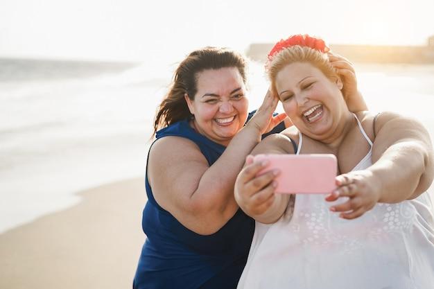 Amigas curvilíneas tirando selfie na praia durante as férias de verão - foco suave no rosto de uma mulher