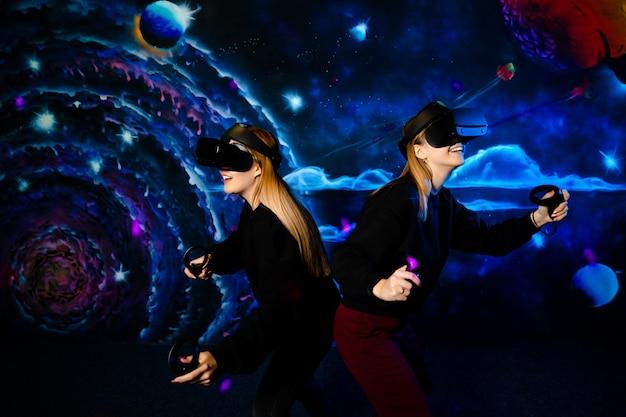 Amigas de duas irmãs com óculos virtuais se divertem juntas e jogam videogame.