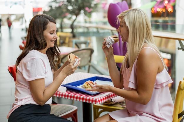 Amigas degustando hambúrgueres juntas em restaurante