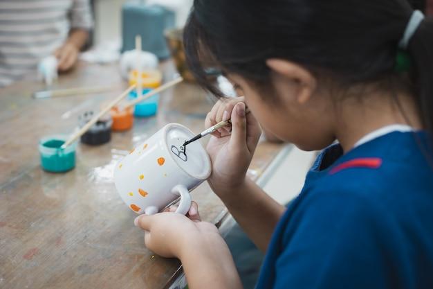 Amigas e amigas crianças asiáticas estão se concentrando para pintar em vidro de cerâmica com tinta a óleo e se divertir. aula de atividades criativas de artes e artesanato para crianças na escola.