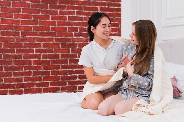 Amigas em casa que compartilham o cobertor