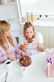 Amigas encantadas comendo um bolo de chocolate na cozinha