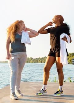 Amigas fazendo saudação de cotovelo enquanto se exercitam na beira do lago