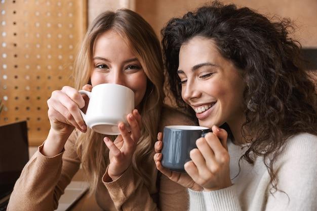 Amigas felizes sentadas em um café conversando e bebendo chá ou café