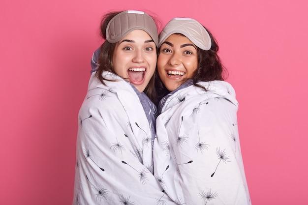 Amigas fofas em traje de noite para uma festa de pijama em fundo rosa