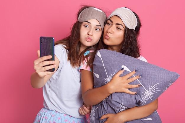 Amigas fofas em traje de noite para uma festa do pijama tirando uma selfie em fundo rosa Foto Premium