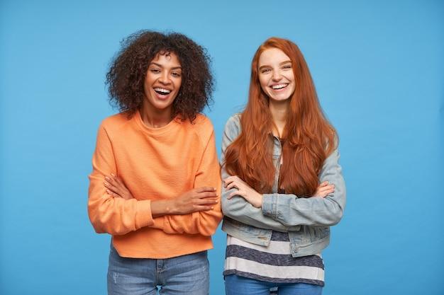 Amigas jovens e amáveis satisfeitas cruzando as mãos no peito em pé sobre a parede azul, estando de bom humor e rindo alegremente enquanto olham