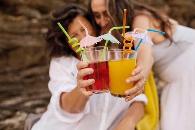 Amigas mais velhas comemorando com coquetéis na praia