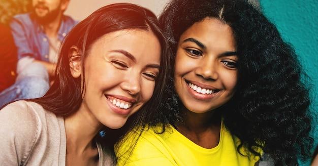 Amigas multiétnicas felizes sentadas nas escadas da escola ou faculdade e se divertindo juntas