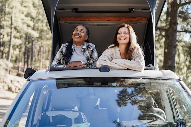 Amigas multirraciais idosas se divertindo dentro de uma van de camping - foco no rosto da mulher africana