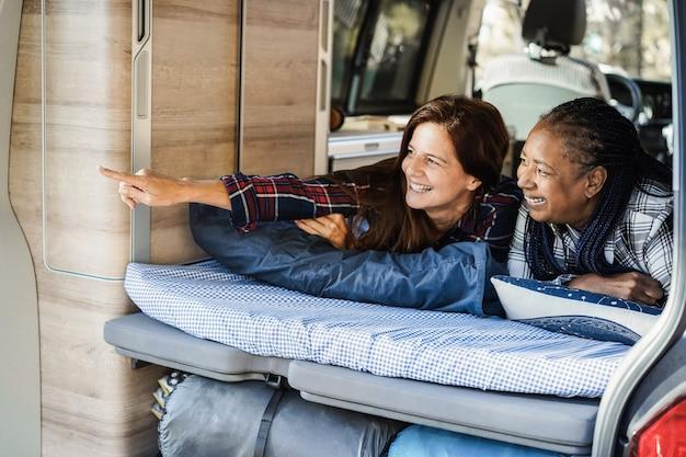 Amigas multirraciais se divertindo acampando dentro de uma van enquanto estão deitadas na cama - foco no rosto feminino africano
