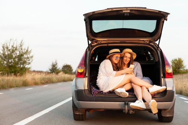 Amigas olhando para o smartphone no porta-malas do carro