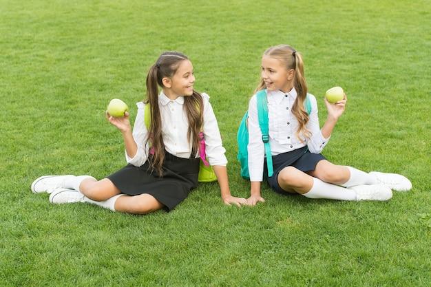 Amigas pequenas comem merenda escolar saudável, conceito de vitamina alimentar.