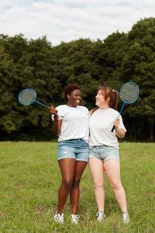 Amigas posando juntas ao ar livre com raquetes de badminton