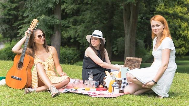 Amigas que apreciam no piquenique no parque
