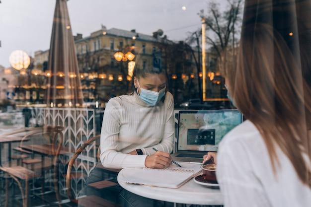 Amigas que as meninas conheceram em um café usam máscaras de proteção médica