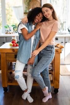 Amigas se abraçando e posando juntas na cozinha