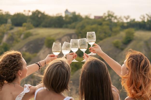 Amigas se divertindo, aplaudindo, bebendo vinho e desfrutando de um piquenique na paisagem de colinas.