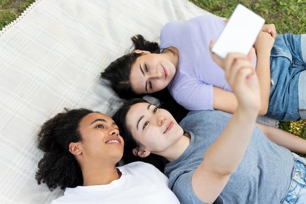 Amigas se divertindo no parque enquanto tomam uma selfie