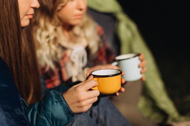 Amigas sentadas em uma barraca tomando chá à noite