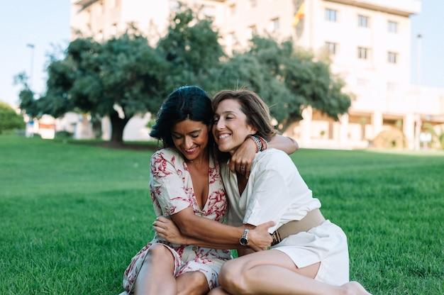 Amigas sentadas na grama, sorrindo e se abraçando
