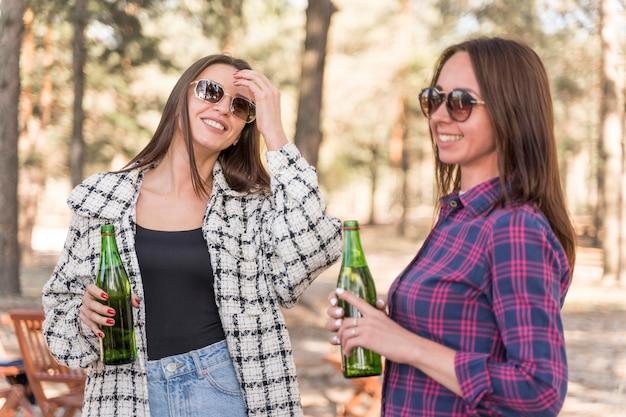 Amigas sorridentes bebendo cerveja ao ar livre Foto gratuita