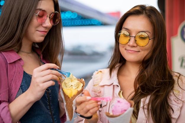 Amigas sorridentes com óculos de sol comendo doces