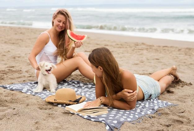 Amigas sorridentes com um cachorro comendo melancia na praia