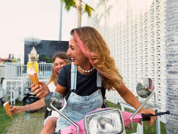 Amigas sorridentes de scooter tomando sorvete
