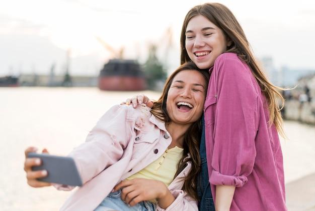 Amigas sorridentes fazendo selfie à beira do lago