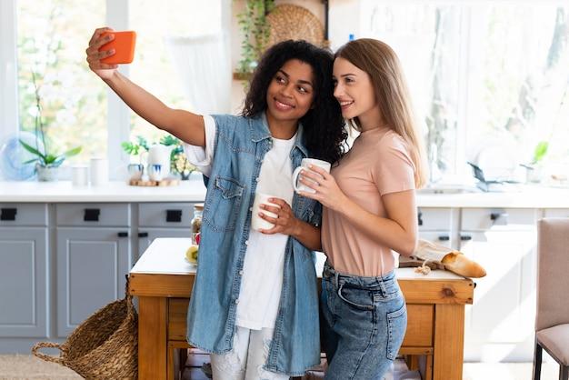 Amigas sorridentes fazendo selfie na cozinha com o smartphone