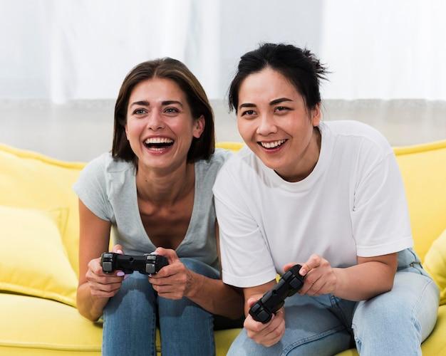 Amigas sorridentes jogando videogame