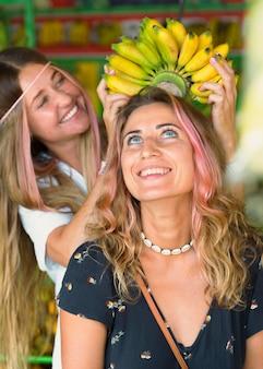 Amigas sorridentes no mercado dos fazendeiros brincando com bananas