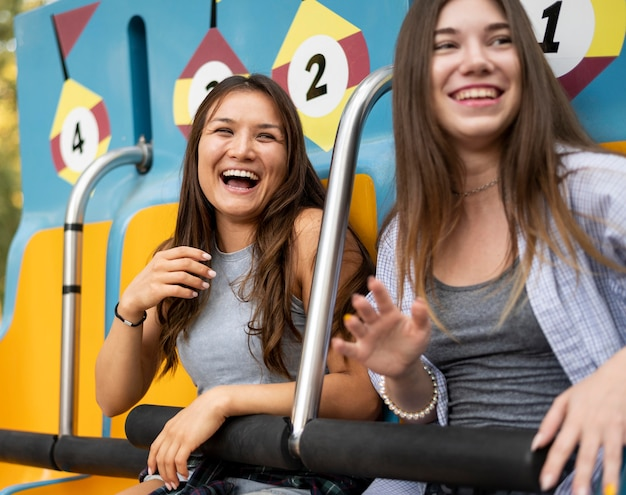 Amigas sorridentes no parque de diversões