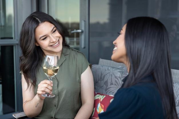 Amigas sorridentes passando um tempo juntas bebendo vinho em um terraço