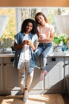 Amigas sorridentes posando na cozinha segurando canecas