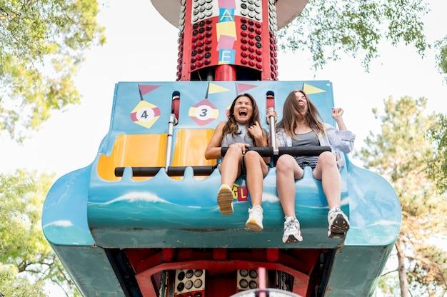 Amigas sorridentes se divertindo no parque de diversões