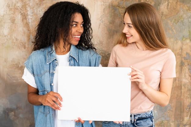 Amigas sorridentes segurando um cartaz em branco