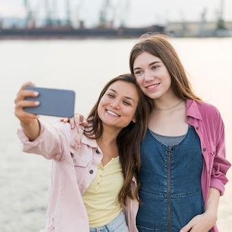 Amigas tirando selfie à beira do lago