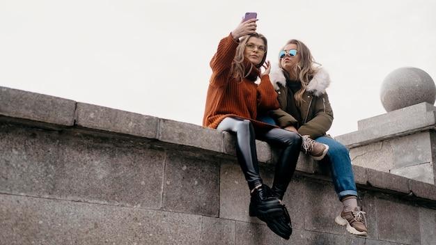 Amigas tirando selfie ao ar livre