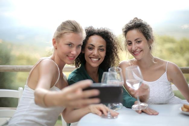 Amigas tirando uma selfie e bebendo taças de vinho