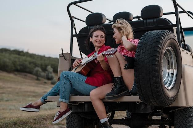 Amigas tocando violão enquanto viajam de carro