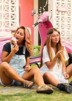 Amigas tomando sorvete ao lado de uma scooter