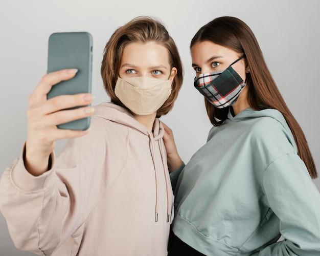 Amigas usando máscaras e tirando selfie