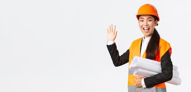 Amigável alegre gerente de construção feminina asiática, arquiteto-chefe de capacete e jaqueta, carrega plantas, documentos de projeto de construção, acenando com a mão para dizer olá, cumprimentando alguém