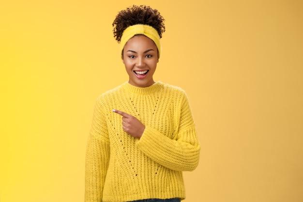 Amigável, bonita e entusiasmada garota negra encantadora no suéter com tiara, sorrindo amplamente divertida, apontando para o lugar incrível para a esquerda, mostrando a você o anúncio de espaço em branco perfeito, posando com fundo amarelo.