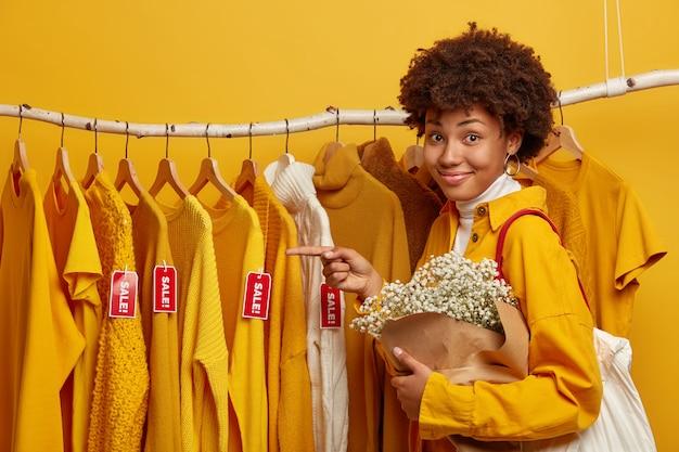 Amigável cliente feminina fica de lado contra o cabideiro, aponta para o suéter com a venda de etiquetas, tem uma sacola de compras no ombro, segura o buquê