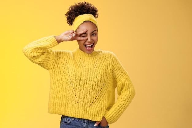 Amigável confiante enérgico afro-americano sorridente menina saudável piscando atitude positiva sorrindo alegre show paz vitória gesto de sorte segurar mão cintura confiante, fundo amarelo.